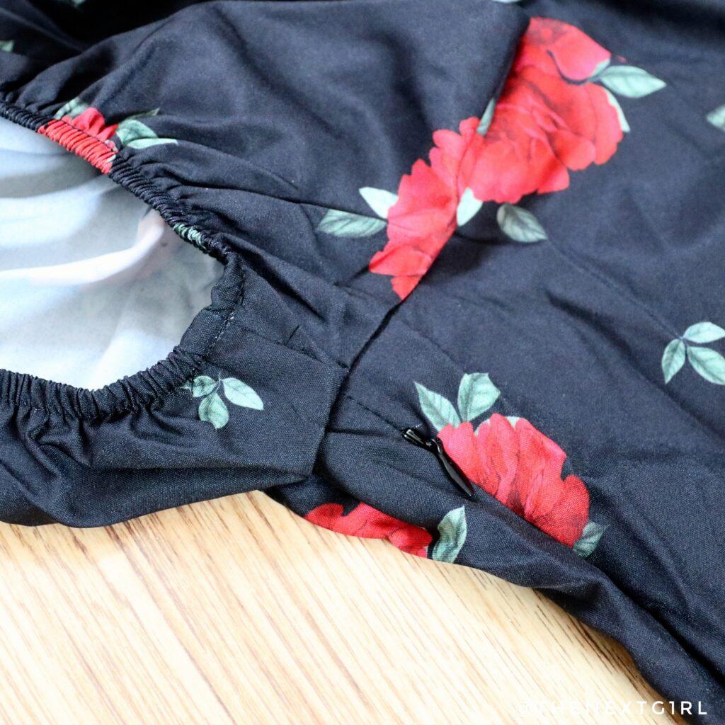 Detail zwart jurkje met rode bloemen